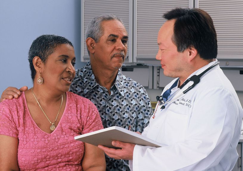 A Hispanic couple consults with an Asian doctor. Image from National Cancer Institute.