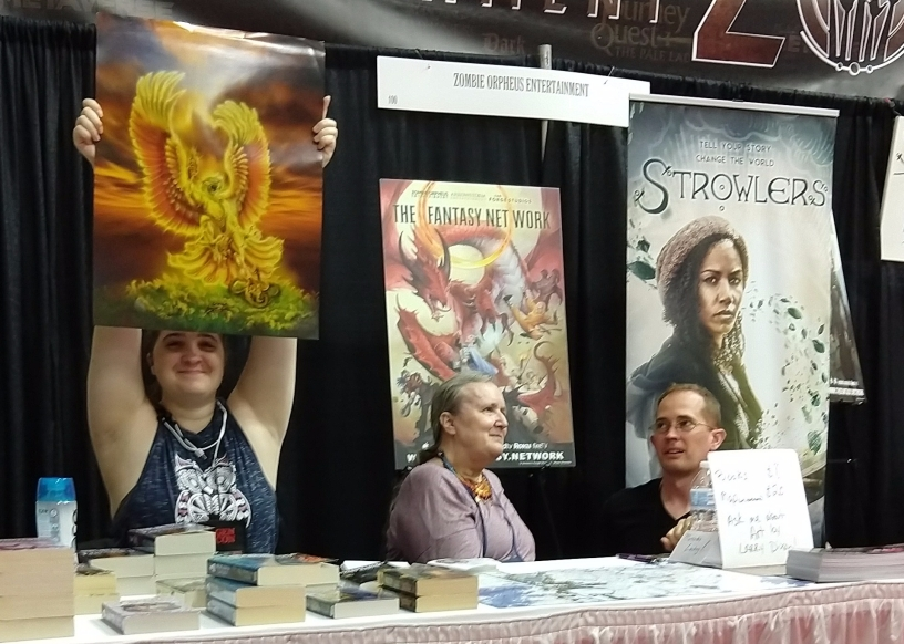 Mercedes Lackey (center) at the Zombie Orpheus Entertainment stall. The person at left holds up a print of one of Larry Dixon's paintings.